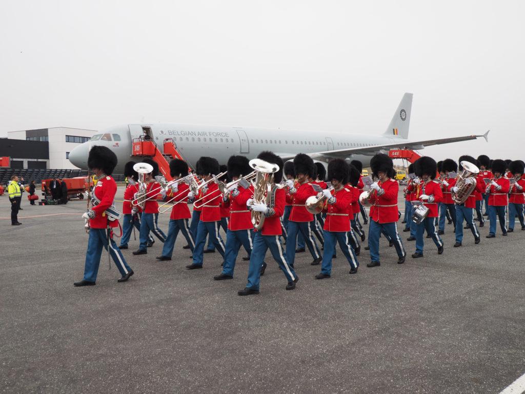 Musikkorpset og Den Kongelige Livgarde forlader flyvepladsen til marchmusik.
